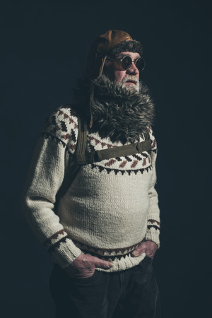 Vintage senior mountaineer with knitted sweater, fur collar and sunglasses. Stock Photo