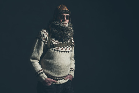 mountaineer: Vintage senior mountaineer with knitted sweater, fur collar and sunglasses. Stock Photo