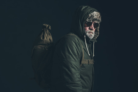 hoody: Vintage bearded mountaineer wearing hoody coat, backpack and sunglasses. Stock Photo