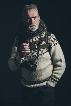 mountaineer: Vintage old mountaineer with knitted sweater, fur collar and SLR camera.