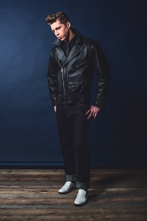 50s fashion: Cool vintage rock and roll 50s fashion man wearing black leather jacket and jeans. Stock Photo