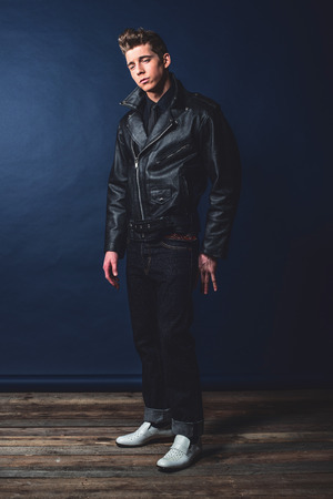 50's: Cool vintage rock and roll 50s fashion man wearing black leather jacket and jeans. Stock Photo
