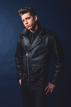 50s: Cool vintage rock and roll 50s fashion man wearing black leather jacket and jeans. Stock Photo