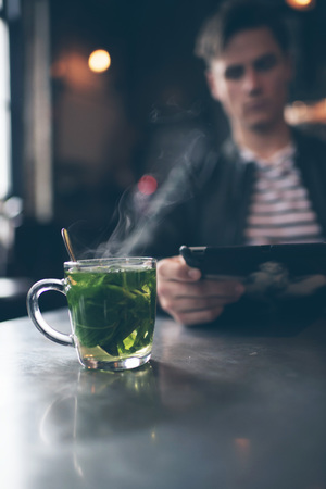 mint tea: Cup of fresh mint tea with blurred man with tablet in bar