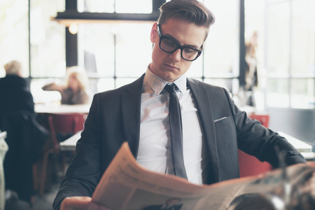 Man in suit with retro glasses reading newspaper in restaurant Stock Photo