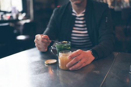 honey blonde: Man in cafe with spoon taking honey out of jar Stock Photo