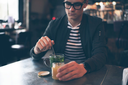 mint tea: Hipster man with retro glasses putting honey in fresh mint tea