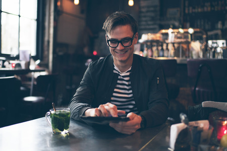 mint tea: Smiling man with retro glasses, tablet and fresh mint tea in cafe