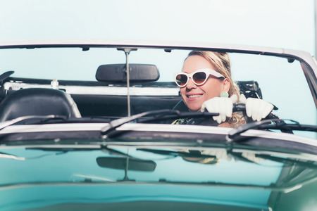 retro woman: Smiling retro 1960s fashion woman with shades driving convertible. Stock Photo