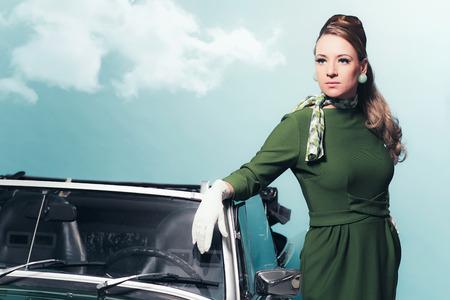 sportscar: Retro 1960s woman in green dress standing next sportscar. Stock Photo