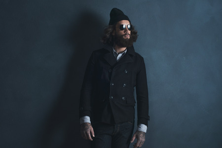70s: Vintage 70s beard man with long hair wearing sunglasses and woolen cap. Standing against gray wall. Stock Photo