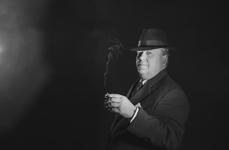 organized crime: Vintage 1930s gangster holding cigar. Classic black and white portrait.