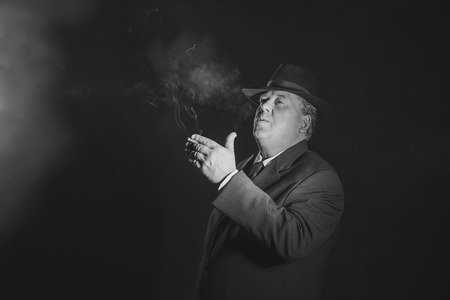 organized crime: Retro 1930s gangster smoking cigar. Classic black and white portrait.