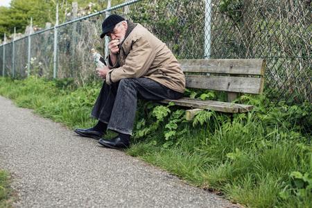 impoverished: Senior homeless man on bench holding bottle.
