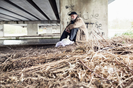 indigent: Wanderer sitting under bridge. Stock Photo