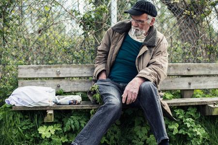 impoverished: Wanderer looking for cigarette lighter.