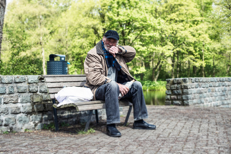 destitute: Homeless man wipes his mouth with his sleeve. Stock Photo