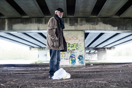 indigent: Lost homeless man standing with bag under bridge. Stock Photo