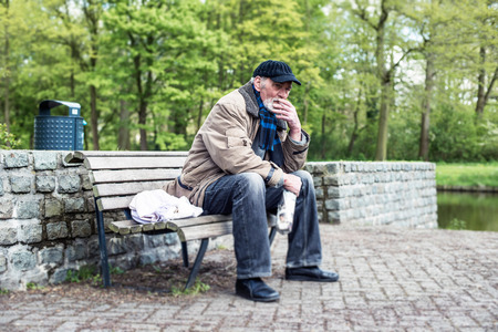 destitute: Smoking homeless man sitting on bench in park.