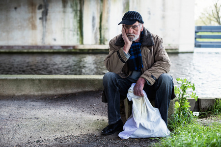 destitute: Depressed homeless man sitting on concrete wall under bridge. Stock Photo