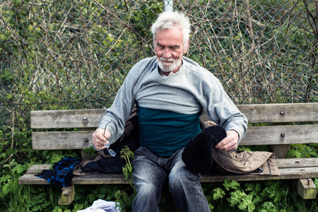 indigent: Homeless man on outdoors bench pulling sweater. Stock Photo