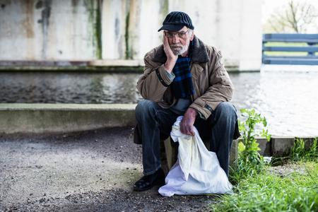 Depressed homeless man sitting on concrete wall under bridge.