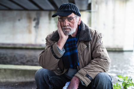 indigent: Depressed homeless man sitting on concrete wall under bridge. Stock Photo