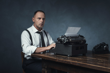 Retro 1940 office worker behind desk with typewriter and telephone. Stock Photo