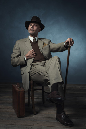 cane chair: Fashionable vintage 1940 business man with cane sitting on chair in room. Stock Photo