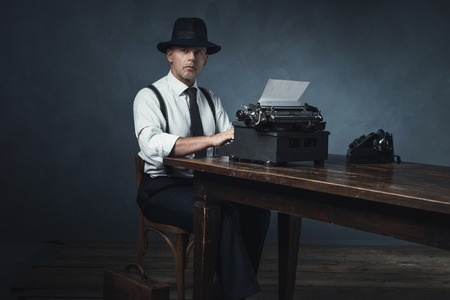 late 40s: Vintage 1940 office worker behind desk with typewriter and telephone.