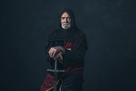 Knight with beard in hauberk holding sword. Stock Photo