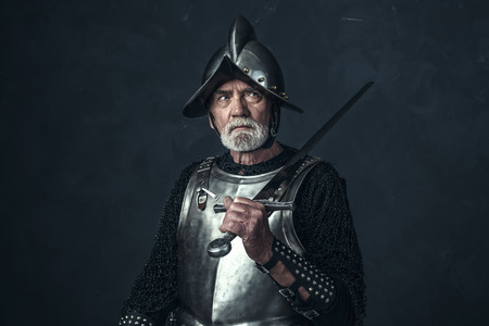 hauberk: Knight in armor with gray beard holding sword.
