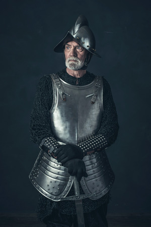 hauberk: Bearded knight standing with sword in front of gray wall.