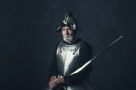 hauberk: Senior knight in armor holding sword. Stock Photo