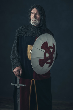 hauberk: Knight with gray beard holding sword and shield. Stock Photo