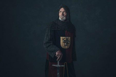 hauberk: Knight with beard in hauberk holding sword. Stock Photo
