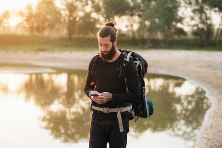 Hiker using cellphone during trip Stock Photo