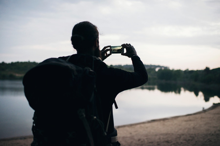 bank records: Silhouette of hiker taking pictures of lake with smartphone