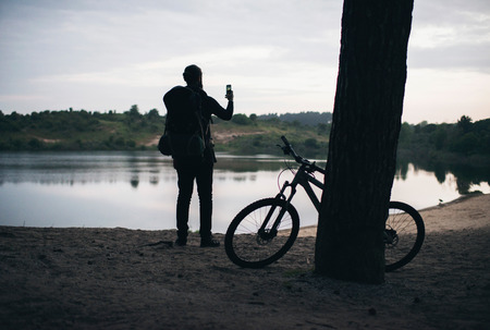 bank records: Backpacker with parked mtb against tree taking pictures of dune lake