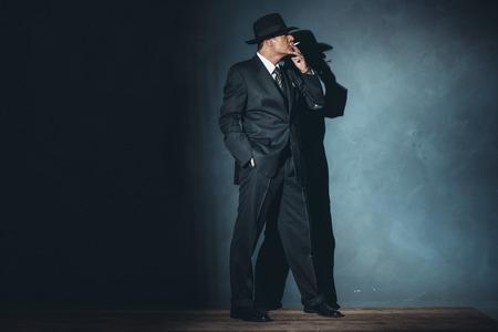 film noir: Film noir man wearing suit and hat. Smoking cigarette. Stock Photo