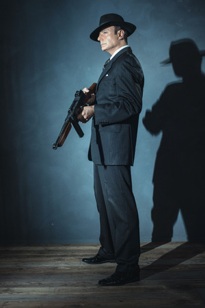 film noir: Film noir gangster shooting with gun.