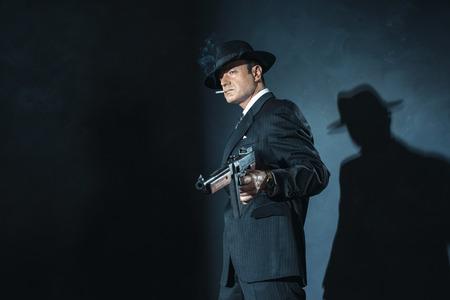 film noir: Retro 1940s film noir gangster with gun smoking cigarette. Stock Photo