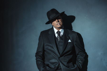 film noir: Retro 1940 film noir gangster wearing suit and hat. Smoking cigarette. Standing against wall. Stock Photo