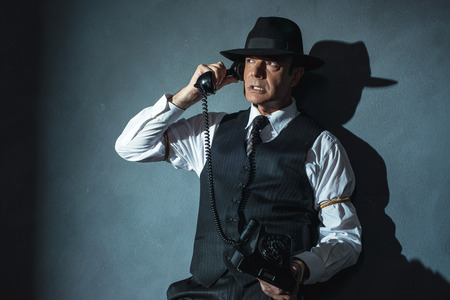 telephone call: Angry retro film noir man calling with old phone.