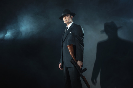 film noir: Retro 1940s film noir gangster standing with gun.