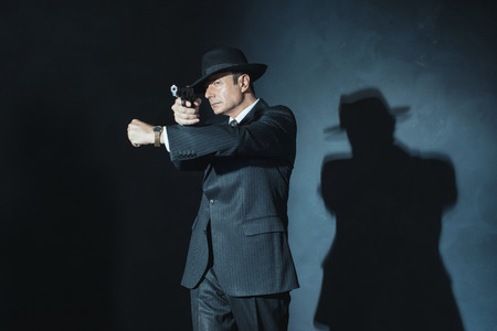 film noir: Vintage film noir 1940s gangster shooting with gun.