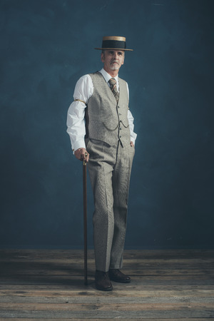 Retro 1920s dandy in suit standing with cane in front of gray wall.