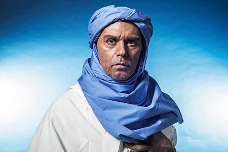 white robe: Berber man wearing blue turban with white robe. Studio shot. Stock Photo