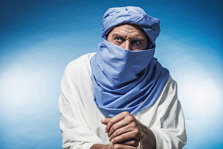 white robe: Berber man wearing blue turban with white robe. Leaning on cane. Studio shot. Stock Photo