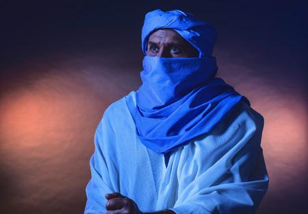 white robe: Berber man in night light wearing blue turban with white robe. Leaning on cane. Studio shot. Stock Photo